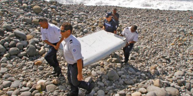 In this photo dated Wednesday, July 29, 2015, French police officers carry a piece of debris from a plane...