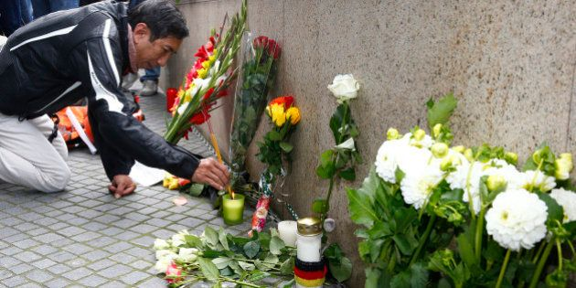 A man lights incense sticks near the Olympia shopping mall, where yesterday's shooting rampage started,...