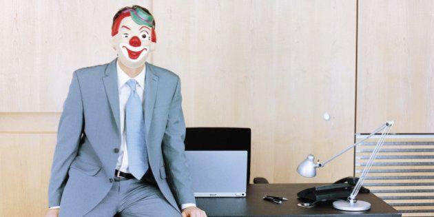 Businessman sitting at edge of desk wearing clown mask
