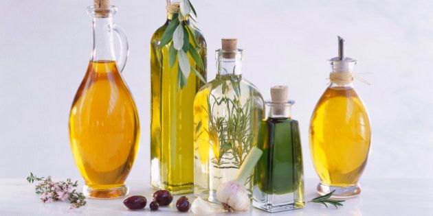 Various oils in bottles with rosemary sprig, olives and garlic