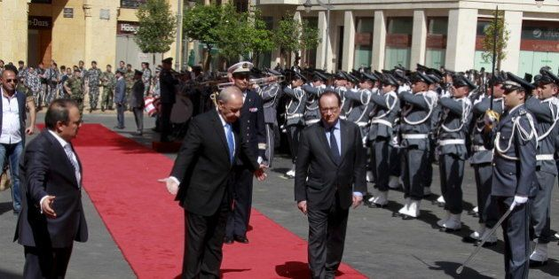 French President Francois Hollande reviews an honour guard with Lebanese Parliament Speaker Nabih Berri...