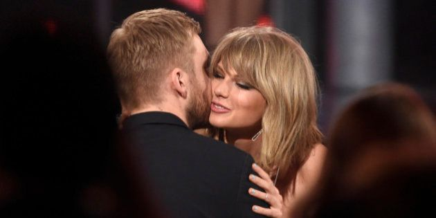"Taylor Swift, right, hugs Calvin Harris after winning the award for top billboard 200 album for ""1989""..."