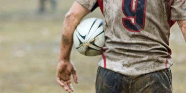 Rear view of bedraggled rugby player in rainy