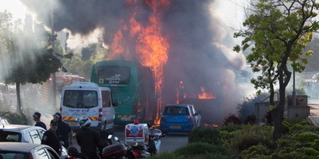 Flames rise at the scene where an explosion tore through a bus in Jerusalem on Monday setting a second...