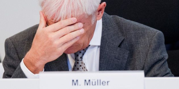 Volkswagen AG CEO Matthias Mueller covers his face with his hand as he attends an employee meeting...