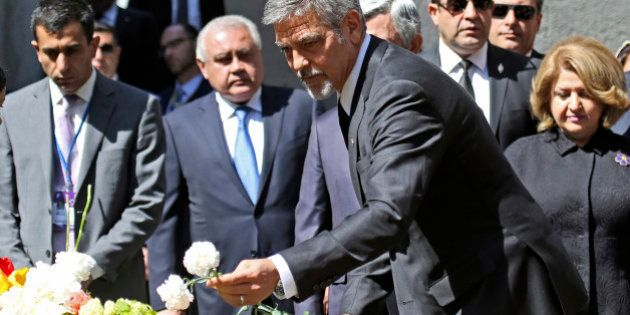 US actor George Clooney, foreground, puts a flower, as he attends a ceremony at a memorial to Armenians...