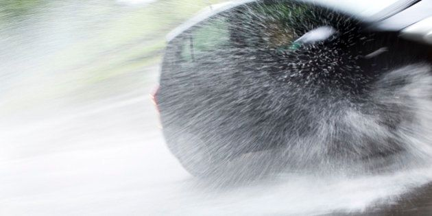 A car sprays a fountain of water as it drives through a large puddle in heavy rain in Berlin, Germany,...