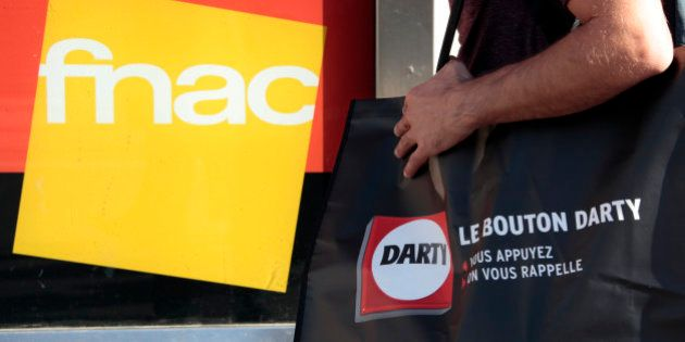 A picture illustration shows a man holding a bag of electrical goods retailer Darty as he stands near...