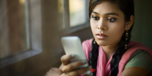 Indoor image in natural light of a beautiful serene Indian girl using smart phone and reading SMS with blank expression. She is sitting wearing traditional dress (Salwar Kameez and Dupatta) near the window of the living room. Waist up, one person, horizontal composition with copy space and selective focus.