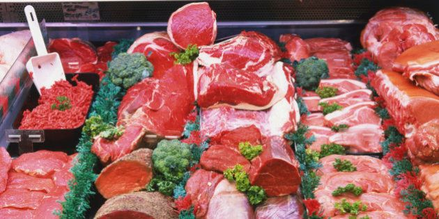 Red meats with herb garnish on display at meat
