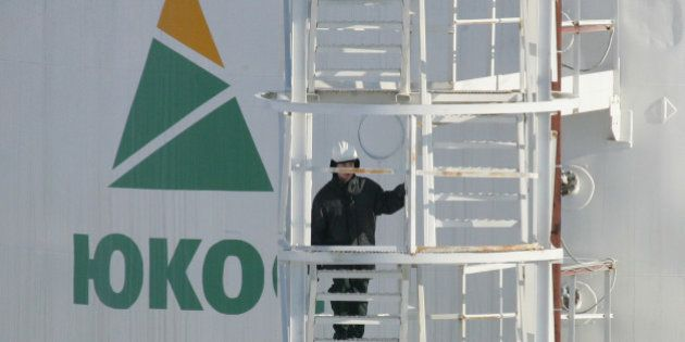 A worker climbs up the stairs of an oil container at the pumping station near the Priobskoye oil field,...