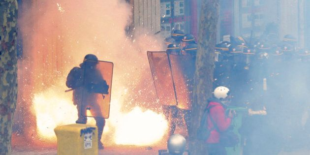 French riot police officers (CRS) face protestors during clashes during a demonstration against the French...