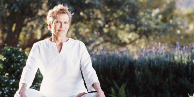Senior woman sitting crossed legged on grass, portrait, ground