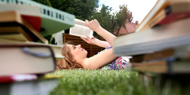 young woman lying on grass in garden reading