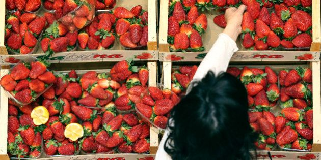 A costumer get a strawberries basket at the Eataly food market store entrance in the former Smeraldo...