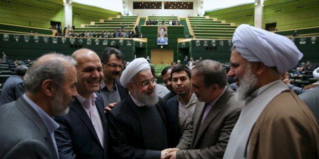 Iranian President Hassan Rouhani (C) is greeted during a session at the Iranian parliament to present...
