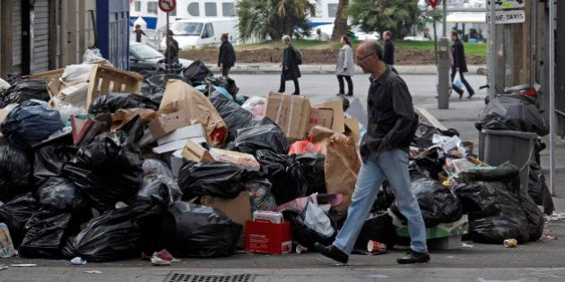 A man walks past piled up garbage at the Old Port of Marseille October 24, 2010 on the 13th day of a...