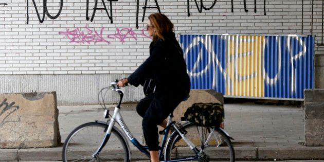 A cyclist rides past graffiti that