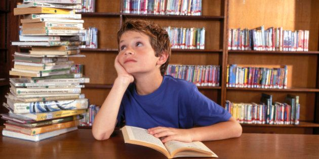 Boy reading by stack of books in