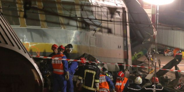 Rescue workers evacuate a victim at the scene where a train derailed at a station in Bretigny sur Orge,...