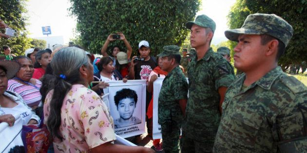 Relatives of missing students protest in front of the entrance to the 27th Infantry Battalion base in...