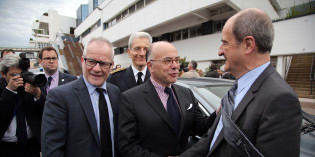 France's Interior Minister Bernard Cazeneuve, center, shakes hand with Cannes Film festival president...