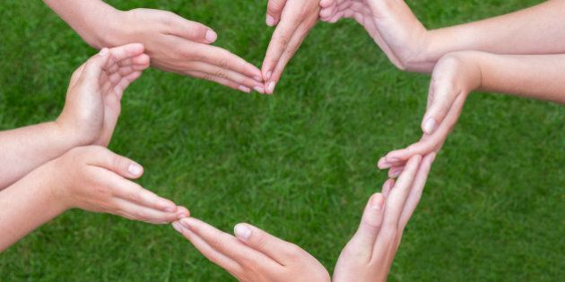 Many arms and hands of girls making heart shape above green grass. Several teens hands joining in figure...