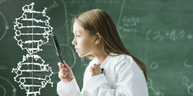 girl in a classroom standing in front of a chalkboard looking at a double helix model with a magnify