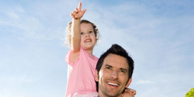 portrait of father carrying little girl on his shoulders