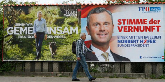 A man passes presidential election campaign posters of Alexander Van der Bellen, supported by the Greens,
