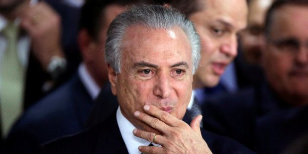 Brazil's interim President Michel Temer gestures during a ceremony where he made his first public remarks...