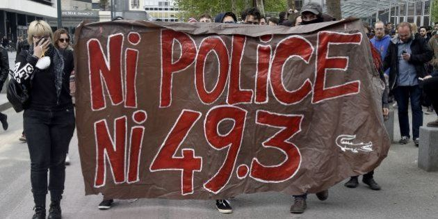 Protesters hold a banner reading 'No police, nor 49.3' on May 14, 2016 in Rennes, western France, during...