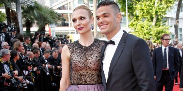 Soccer player Hatem Ben Arfa (R) poses on the red carpet as he arrives for the screening of