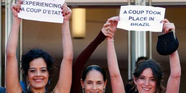 Cast members Maeve Jinkings (L) and Sonia Braga (C) hold placards to protest against the impeachment...
