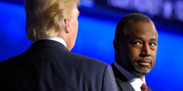 Ben Carson watches as Donald Trump takes the stage during the CNBC Republican presidential debate at...