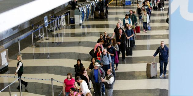 A long line of travelers wait for the TSA security check point at O'Hare International airport, Monday,...