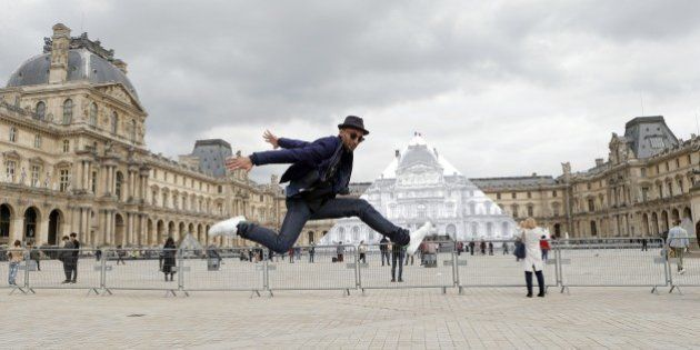 Street artist JR poses in front the Louvre Pyramid in Paris, Tuesday, May 24, 2016. For his latest bold...