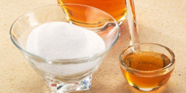 Honey in glass jar and in small bowl with spoon inside, and bowl of white sugar