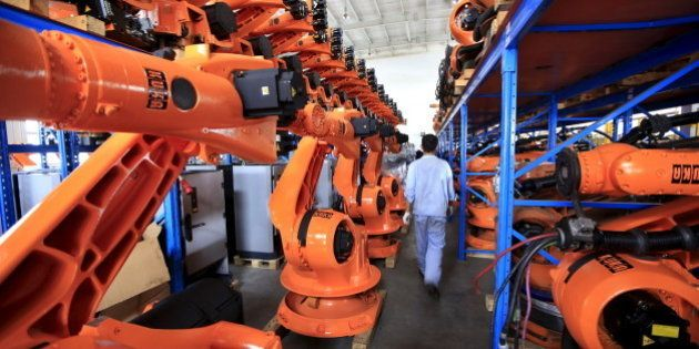 A worker walks past second-hand robots in a factory in Shanghai, August 21, 2015. More than a hundred...