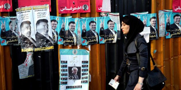 An Iranian woman walks past electoral posters of parliamentary election candidates on a sidewalk in downtown...