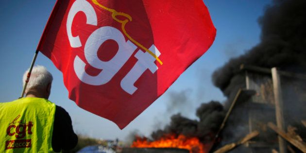 A striking French CGT labour union employee stands near a burning barricade during a police operation...