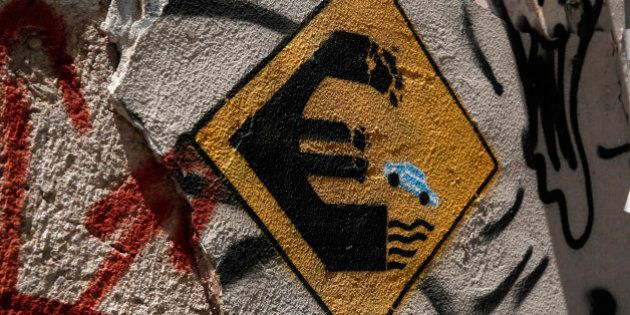 Graffiti depicting a car driving off a euro sign into water on a wall of an abandoned house in Athens,...
