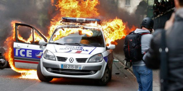 A police car burns during a demonstration against police violence and against French labour law reform...