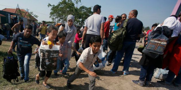 Migrants run to a bus which will take to the border with Hungary, in front of a migrant camp close to...