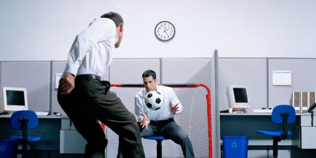 Two businessmen playing soccer in office, goalie catching