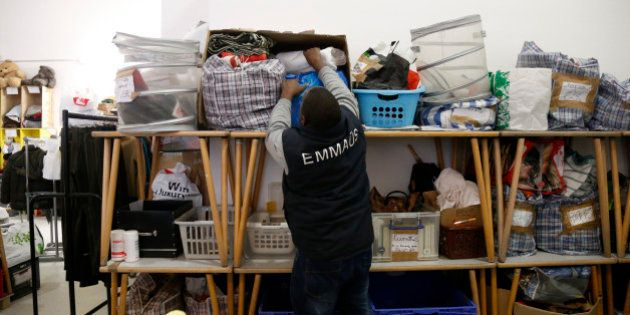 An employee selects second-hand items at the Emmaus Defi Bric a Brac show room in Paris November 16,...