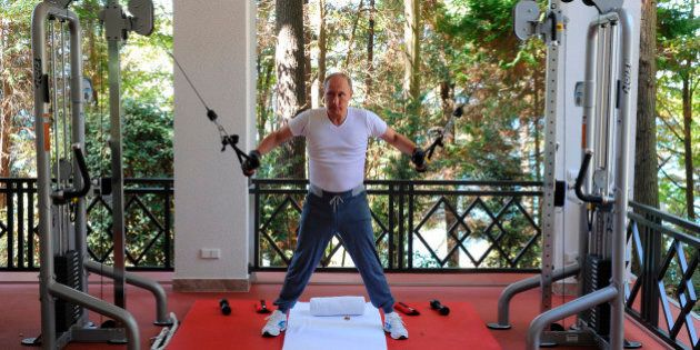 Russian President Vladimir Putin exercises during his meeting with Prime Minister Dmitry Medvedev, unseen,...