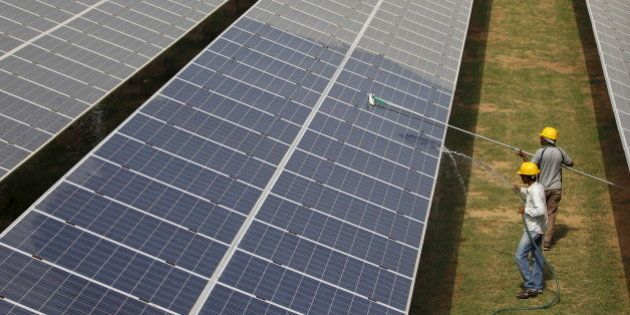 Workers clean photovoltaic panels inside a solar power plant in Gujarat, India, in this July 2, 2015...