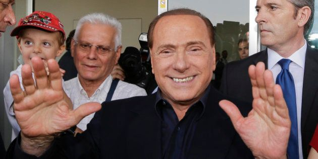 AC Milan president Silvio Berlusconi waves to supporters outside the Milanese soccer club's headquarters,...