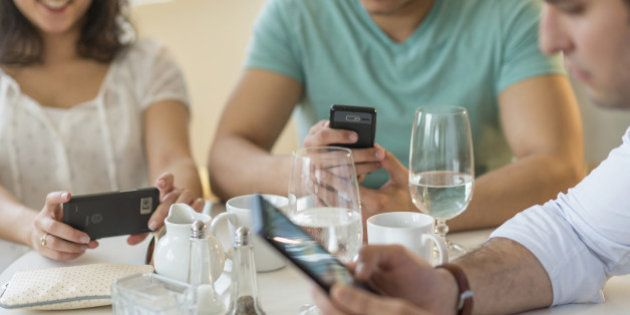 Hispanic friends using cell phones in
